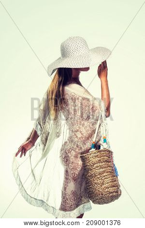 Woman in summer beach outfit and straw hat