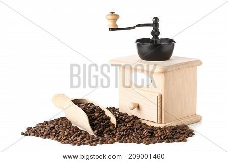 Coffee beans in wooden scoop with wooden coffee bean grinder over white background