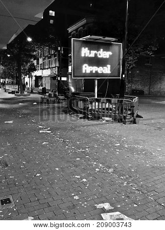 Screen in Town centre at night. Black and white photography. Murder Appeal.