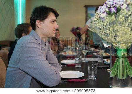 sitting guests invited to feast eat at table, young man in foreground waiting for food, empty plate