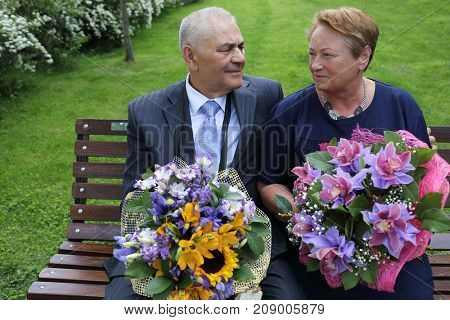 portrait of family elderly couple, man and woman sitting on wooden bench, holding bouquets of flowers in their hands