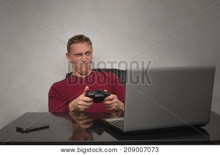 Emotinal gamer. Young man goes angry when playes in game. Young hysterical man with joystick.