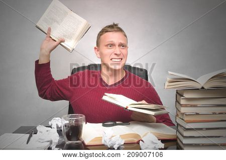 Young student man becomes hysterical from studying and throws up text book away. Business man goes crazy with overload at work. Hard job.