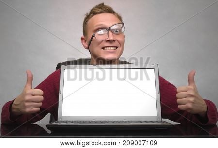 A successful smiling young business man in glasses showing thumbs up sign symbol behind blank screen of laptop computer on the table. Special offer. Big sale. Contact us. Winner. Lucky.