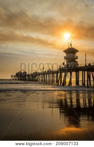 Local wildfires pipeline golden brown smoke over the skies of Huntington Beach pier, creating surreal scenery.