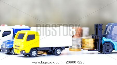 Golden coins stacked on the forklift truck on gray background. The concept of business growth financial or money savings