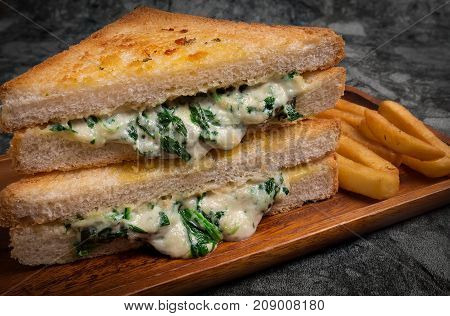 Vegetarian pressed double panini with young spinach leaves, onions and cheese served  with French fries and sauce on the wooden plate.