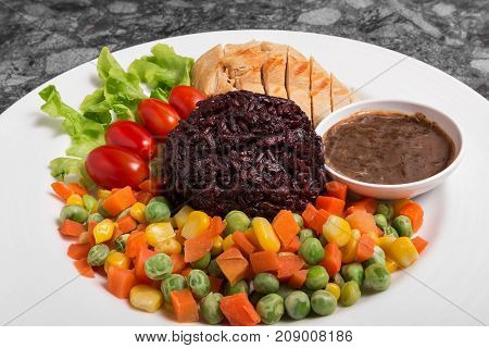 Clean food Riceberry rice with Chicken Breast serve with boiled Vegetables and good for you health in white dish.