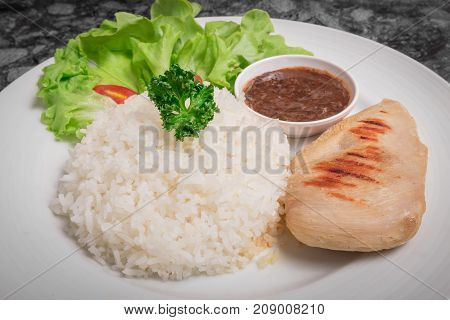 Clean food. Rice with Chicken Breast and Teriyaki sauce with vegetable in white dish.