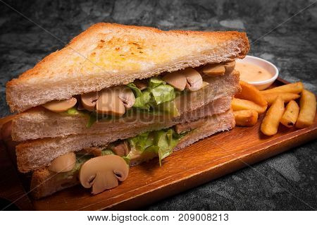 Tasty Sandwich with mushrooms serve with French fries and sauce on the wooden plate.