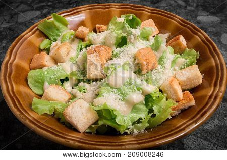 Caesar salad with cream sauce on top with croutons in plate.