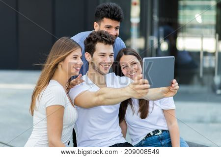 Group of friends taking selfie with a tablet