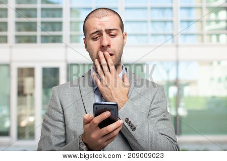 Concerned businessman looking at his mobile phone