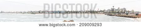 SWAKOPMUND NAMIBIA - JUNE 30 2017: A misty panorama of the Molen the Strand Hotel the lighthouse and apartments in Swakopmund