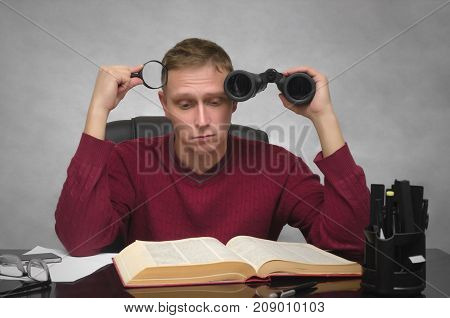 Yound student man with binoculars and magnifier in hands tired of studying and searching information. Business man tired of boring work. Hard job. Find and search.