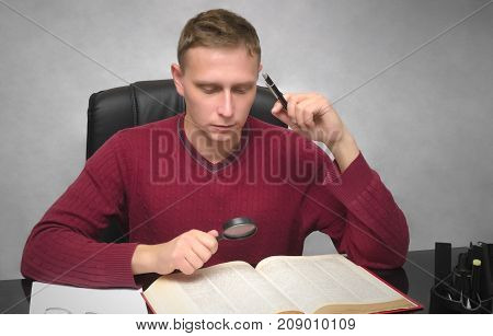 Find and search. Young student with magnifier and pen in hands studying school homework. Young business man looking for some information. Office work.