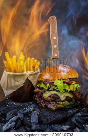 Tasty smoked grilled and glazed beef burger with lettuce, cheese and bacon served with french fries on wooden table with copyspace, smoke and fire wood in background.