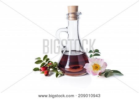 Syrup from a dogrose in a decanter hips green leaves and flowers with buds isolated on a white background