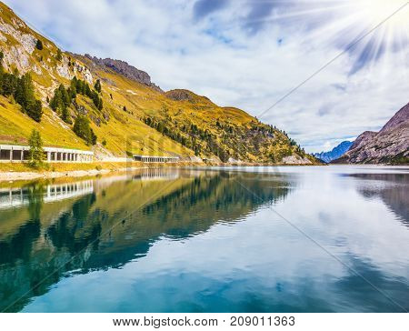 Glacial lake with clear cold water. Mountain Lake Lago di Fedaia, Dolomites. The concept of ecological and extreme tourism. The magic and harmony of the Dolomites