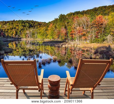 Flock of migratory birds flies over the lake. Wooden comfortable loungers on the shore of the lake. Resort in French Canada - Mont Tremblant. Concept of ecological tourism
