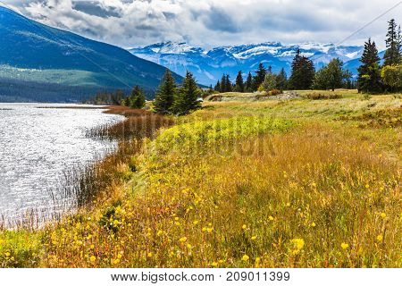 Rocks, lakes and yellow grass under flying clouds. Trip to the Rockies of Canada. Concept of active automobile and ecological tourism