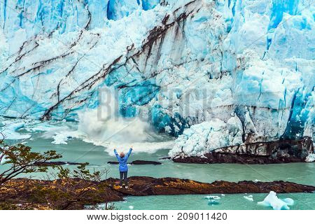 Patagonia. Woman - tourist is standing in front of a blue ice wall. Unique lake and glacier Perito Moreno. The concept of  exotic and extreme tourism