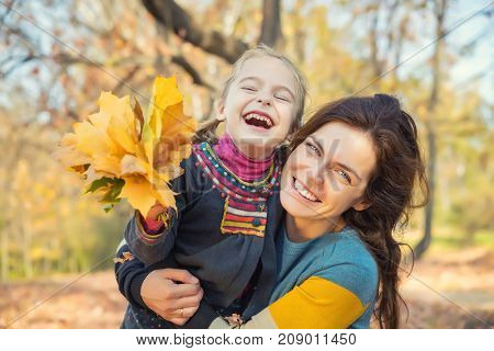 Little girl and her mother playing with bright autumn leaves in the autumn park