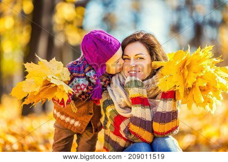 Little girl playing with mother in the autumn park
