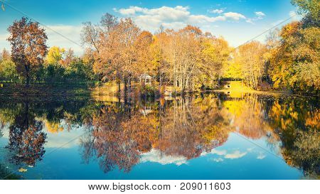 Sunny autumn landscape with blue sky over lake