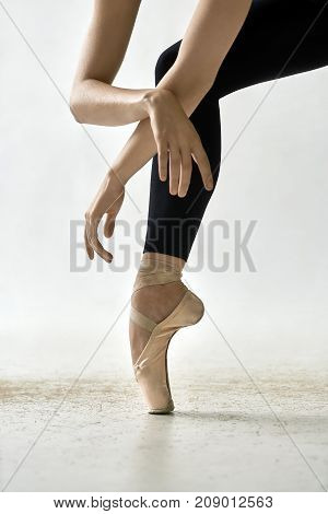 Cute ballerina is posing in the studio on the light background. She stands on the toe and holds crossed arms on the leg. Girl wears black leggings and beige pointe shoes. Closeup. Vertical.