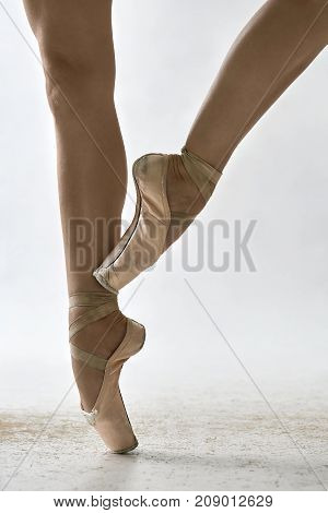 Ballerina is posing in the studio on the light background. She stands on the right toe and holds left foot on the right leg. Girl wears beige pointe shoes. Closeup. Vertical.