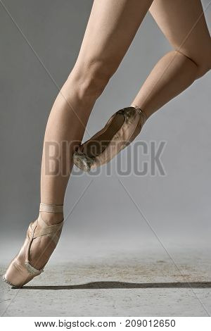 Amazing ballerina is posing in the studio on the gray background. She stands on the right toe and holds left foot on the right leg. Girl wears beige pointe shoes. Closeup. Vertical.