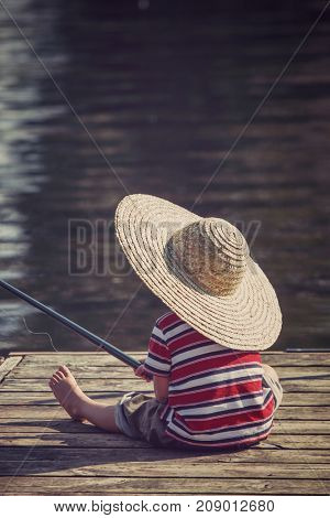 Young boy wearing a straw hat fishing, vintage toned