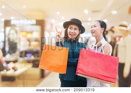 Happy woman with shopping bags in modern department store or shopping center. Woman lifestyle and fashion concept.