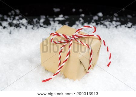 Vintage Paper Wrapped Gift Tied With Red And White Striped Twine Sitting In Snow