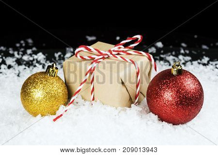 Old Fashioned Gift Wrapped In Plain Paper, Tied With Red And White Twine Sitting In Snow Beside Holi
