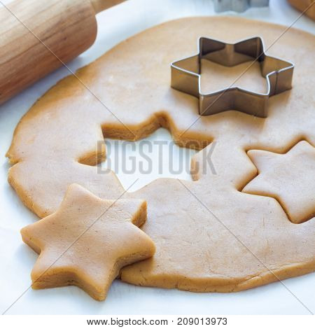 Making gingerbread cookies. Dough metal cutter and rolling pen on wooden table square format