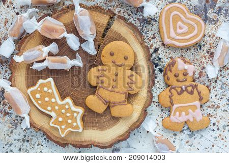 Christmas gingerbread cookies and caramel candies on a wooden board horizontal top view