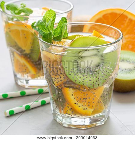 Healthy detox chia seed drink with kiwi orange and mint in a glass square format