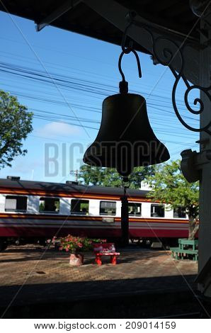 Beautiful background ,Train station Silhouette brass bell on the platform of the station , Thailand train station