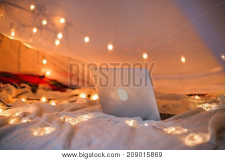 the laptop lies on the bed in the background of a Christmas-tree light