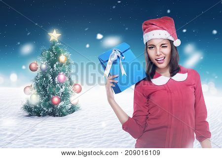 Asian woman wearing santa hat holding present with christmas tree background