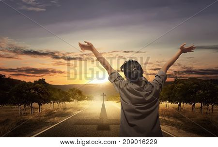 Back View Of Woman Raising Hand With Open Palm While Praying