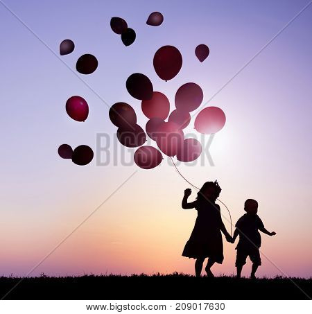 Children Outdoors Holding Balloons Together