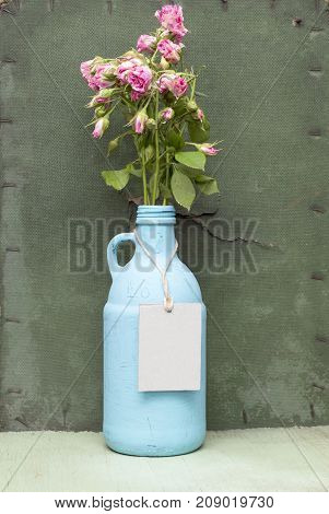 Painted blue bottle with kraft lable. Grunge green wooden background. Old bottle tag mock-up. Blue jug with pink roses