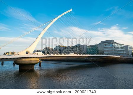 DUBLIN IRELAND - AUGUST 10 2017; Also known as the Harp striking architecturaly modern white cable stay bridge across Liffey River in glow of sunrise.