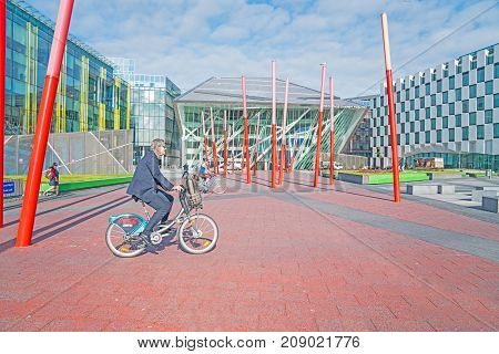 DUBLIN IRELAND - AUGUST 10 2017; Commuters cycle and walk through Grand Canal Square public space surrounded by modern architectural buildings and red pole sculpture on way to work.