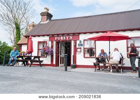 TRIM IRELAND - AUGUST 11 2017; group of local men sit under umbrella drinking beer outside Furey's traditional Restaurant Ireland on old Dublin to Trim road.