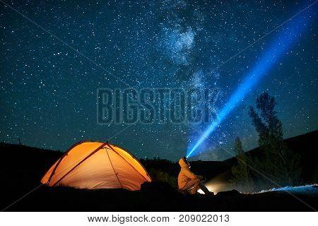 Man tourist with flashlight near his camp tent at night under a sky full of stars. Orange illuminated tent.