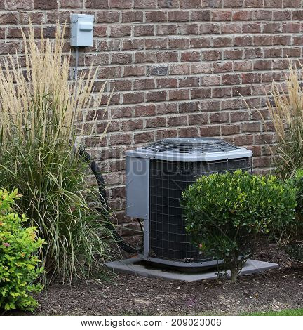 Air Conditioning Outdoor Unit Surrounded by Shrubs
